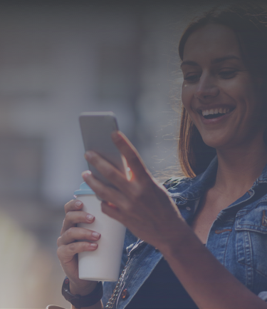 Woman holding coffee cup and smiling while she looks at phone